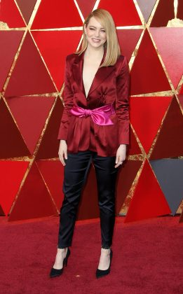 Emma Stone looked every inch a winner on the red carpet of the 2018 Oscars wearing a burgundy tux-style jacket with a hot pink sash around her waist. (Photo: WENN)