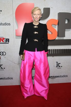 "Tilda Swinton arrived at the ""Suspiria"" L.A. premiere wearing hot pink, silk taffeta giant trousers by Schiaparelli, and a black blazer with gold hands for buttons. (Photo: WENN)"