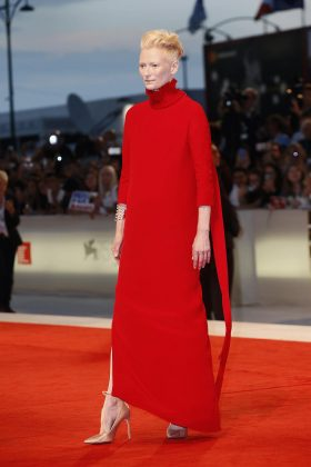 "The actress opted for an avant garde look at the Venice Film Festival premiere of ""Suspiria"" wearing a red column dress with a Victorian-inspired ruffle collar. (Photo: WENN)"