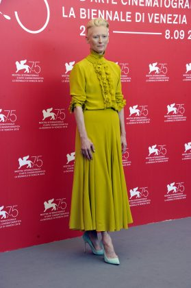 """Tilda Swinton stand out in a chartreuse dress with a structured, high neck with ruffled detailing at the photocall at the Venice Film Festival for """"Suspiria."""" (Photo: WENN)"""