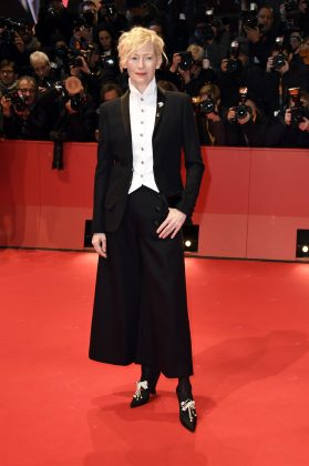 """Swinton promoted her movie """"Isle of Dogs"""" at the 2018 Berlin Film Festival wearing a tuxedo jacket and pair of wide-legged trousers with a wing-tipped shirt. (Photo: WENN)"""