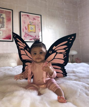 For her first Halloween, Stormi wore an all pink outfit and jacket with a matching pair of butterfly wing and a giant grin. (Photo: Instagram)