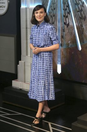 Millie Bobby Brown lighted up the Empire State Building to honor World Children's Day while wearing an Altuzarra button-up blue plaid dress. (Photo: WENN)