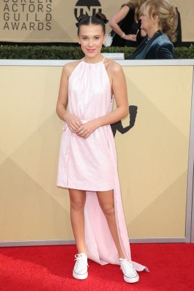 Millie Bobby Brown's pink sequined, high-low Calvin Klein dress and white classic Converse combo at the 2018 SAG Awards was fun meets black-tie. (Photo: WENN)