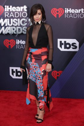 The Cubana rocked a sheer black bodysuit featuring a white triangle collar and a colorful skirt at the 2018 iHeartRadio Music Awards. (Photo: WENN)