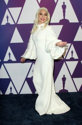 Gaga entered the room at the 2019 Oscar nominees' luncheon in a white Louis Vuitton gown with ruffled bell sleeves. (Photo: WENN)