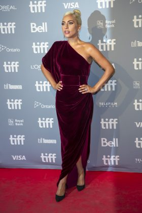The actress sported a burgundy velvet, one shoulder ready-to-wear gown by Ralph and Russo for the 'A Star Is Born' TIFF press conference. (Photo: WENN)