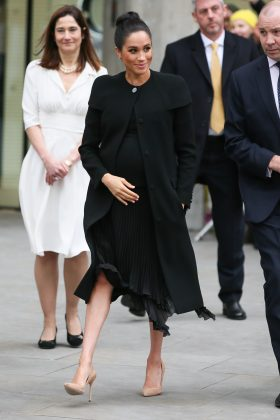 The Duchess of Sussex looked incredible in a black Givenchy coat and pleated dress during her ACU visit. (Photo: WENN)