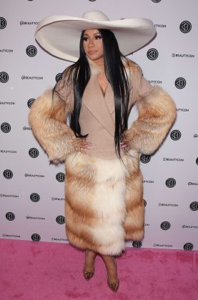 Cardi B made her grand arrival at Beauty Con NYC in a full-length fur ensemble and massive flappy hat. (Photo: WENN)