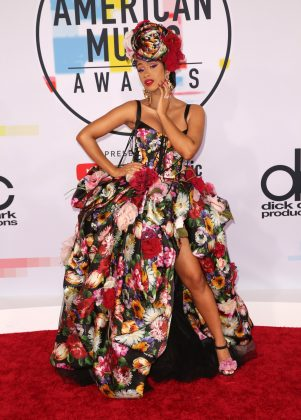 Cardi attended the 2018 AMAs in a dramatic ball gown and matching headdress, all covered in a brightly colored floral pattern. (Photo: WENN)
