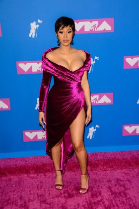 The rapper hit the red carpet at the 2019 VMAs in a asymmetrical off-the-shoulders velvet-plum dress, complete with thigh-high slit. (Photo: WENN)