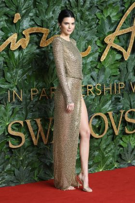 The model wore a completely naked gold sparkly dress to the 2018 British Fashion Awards. (Photo: WENN)