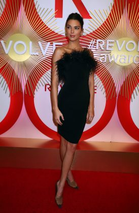 "The ""it girl"" attended the Revolve Awards 2018 in a black figure hugging dress, detailed with a feather trim. (Photo: WENN)"