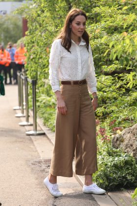 Kate returned to the Chelsea Flower show wearing a casual look: wide-legged tan culottes, a cream blouse, and matching sneakers. (Photo: WENN)
