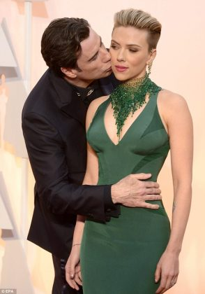 John Travolta photobombed Scarlett Johansson on the Oscars red carpet and planted a huge smacker on her check, much to her dismay. The photos went viral. (Photo: WENN)
