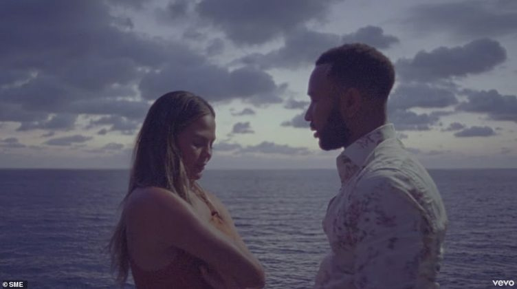 Chrissy Teigen and John Legend announce they are expecting third child with close-up shot of her growing bump in new Wild video (Photo: Release)