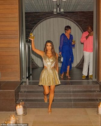 The reality star raised a tropical drink as she descended down a staircase (Photo: Instagram)